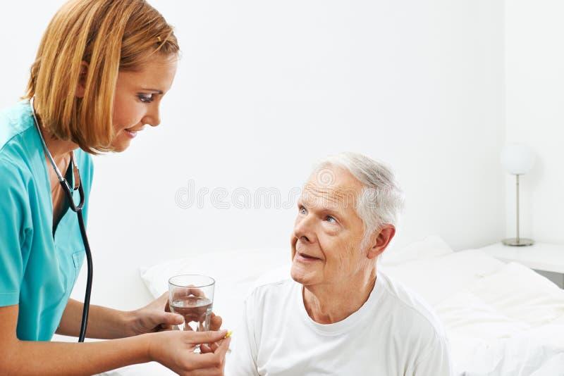 Viejo hombre que consigue la medicina de enfermera foto de archivo