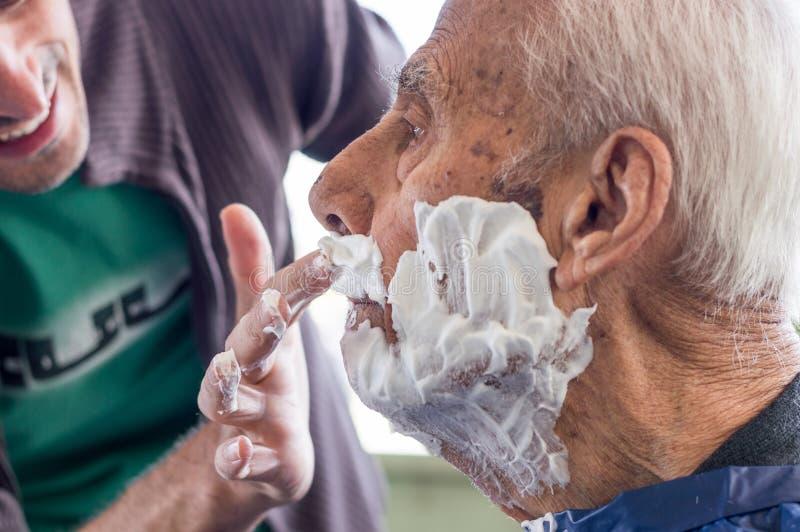 Viejo hombre que consigue su barba afeitada por el hombre experto joven en casa fotografía de archivo libre de regalías