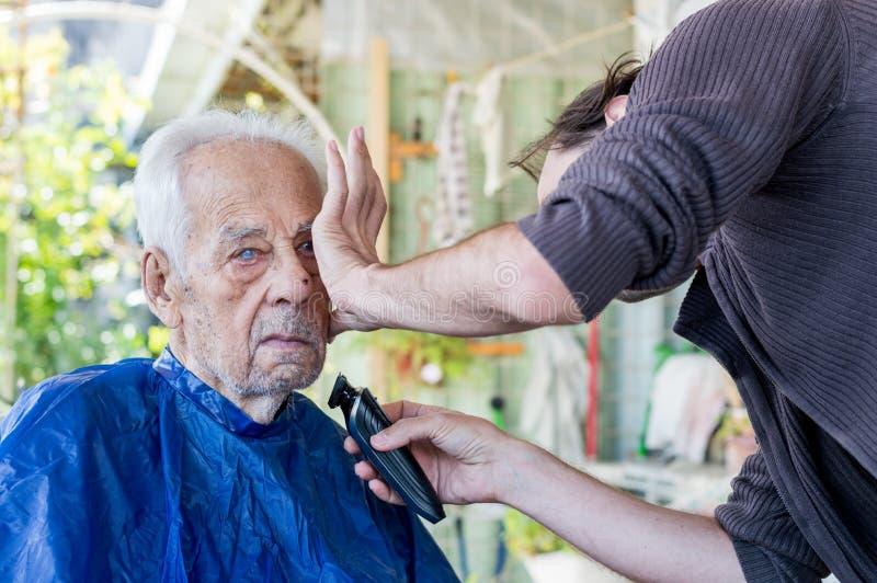 Viejo hombre que consigue su barba afeitada por el hombre experto joven en casa fotos de archivo libres de regalías