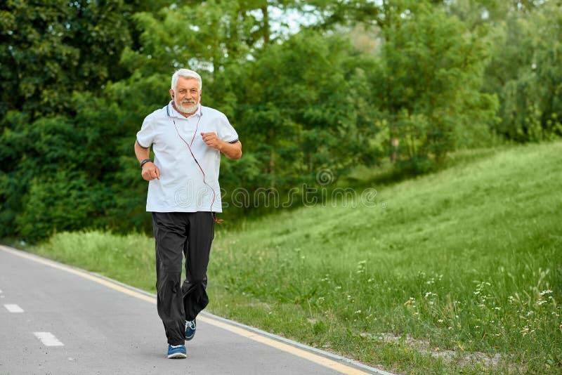 Viejo hombre que corre en pista moderna del ` s del parque de la ciudad foto de archivo