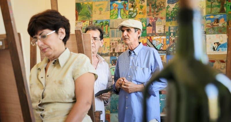 Viejo hombre que enseña a los estudiantes de Art Professor Working With Senior fotografía de archivo libre de regalías