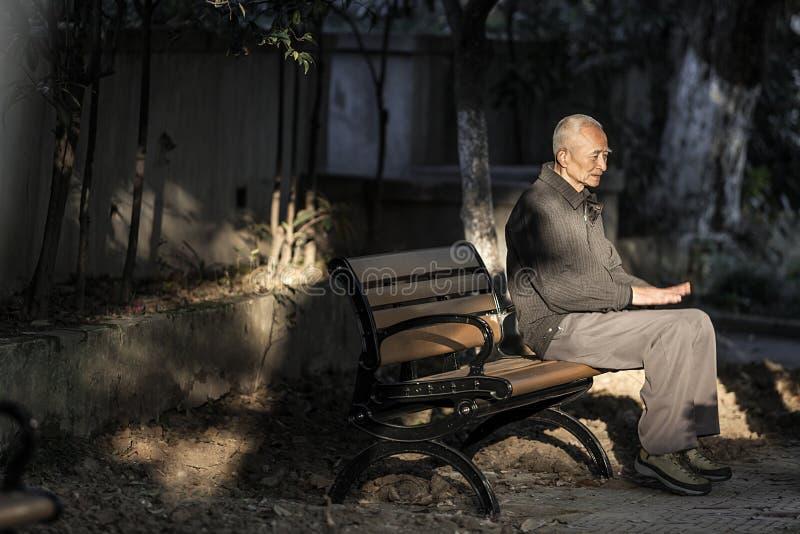 Viejo hombre que está haciendo ejercicios de pierna en el parque foto de archivo