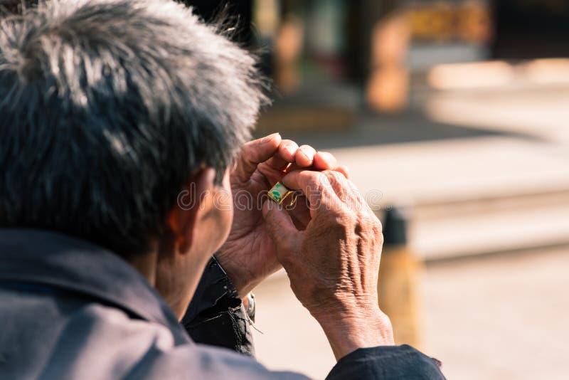 Viejo hombre que examina un anillo de oro en un mercado fotografía de archivo