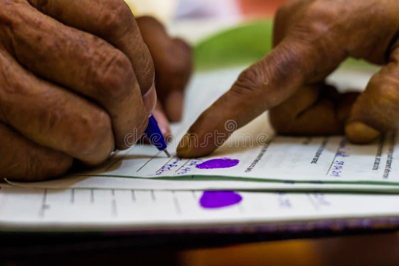 Viejo hombre que firma en un documento jurídico imoirtant según lo dado instrucciones fotografía de archivo libre de regalías