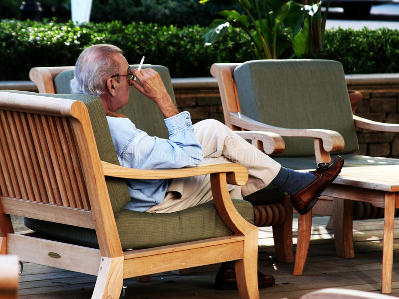 Viejo Hombre Que Fuma En Una Silla Fotografía de archivo libre de regalías