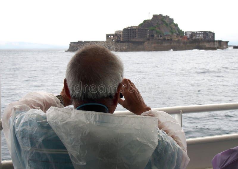 Viejo hombre que hace turismo cerca de Gunkanjima Hashima o de la isla del acorazado fotografía de archivo libre de regalías