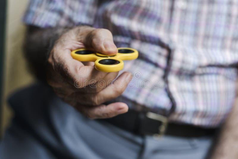 Viejo hombre que juega con un hilandero de la persona agitada fotografía de archivo
