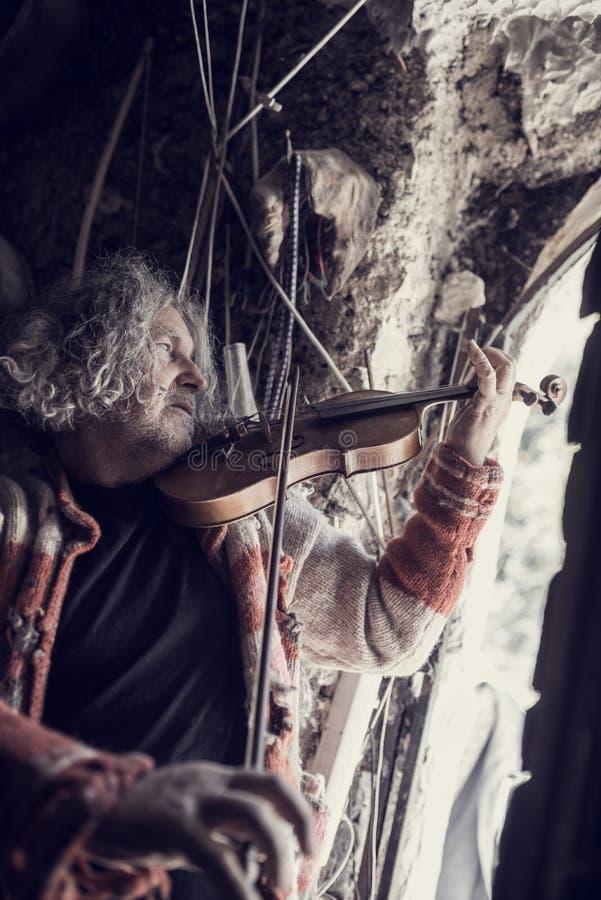 Viejo hombre que juega música en un violín de madera clásico fotos de archivo libres de regalías
