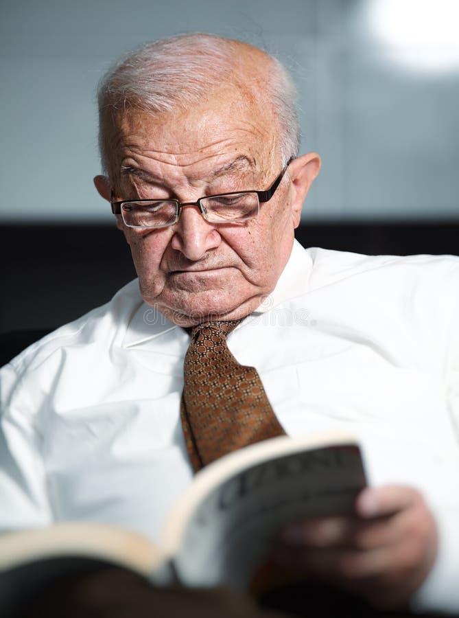 Viejo hombre que lee un libro foto de archivo libre de regalías