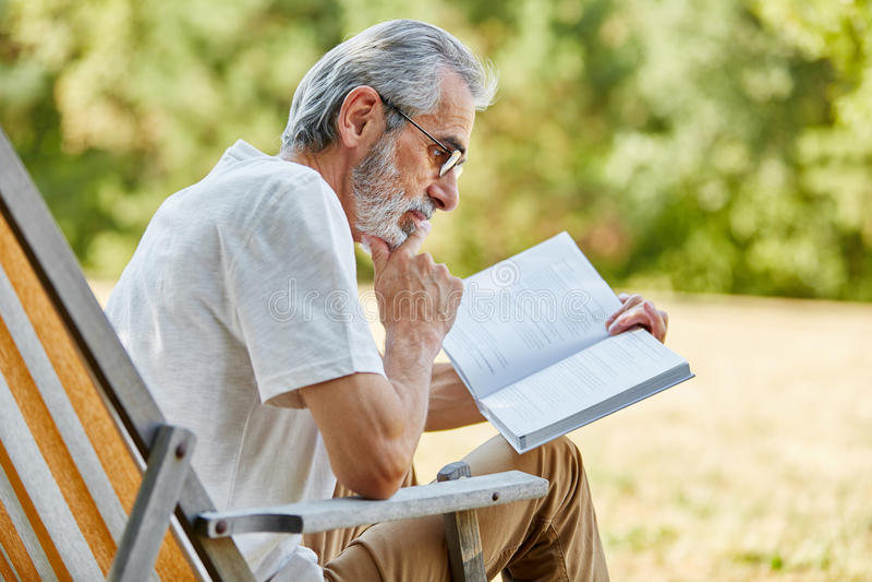 Viejo hombre que lee un libro en una silla de cubierta fotos de archivo
