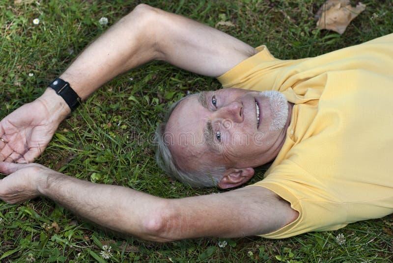 Viejo hombre que miente en la hierba foto de archivo libre de regalías
