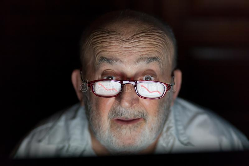 Viejo hombre que mira la pantalla de ordenador con la línea reflexión del beneficio sobre sus vidrios imagenes de archivo