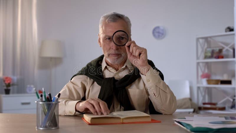 Viejo hombre que mira a través de la lupa, tiempo libre con placer, ojo agrandado imagenes de archivo