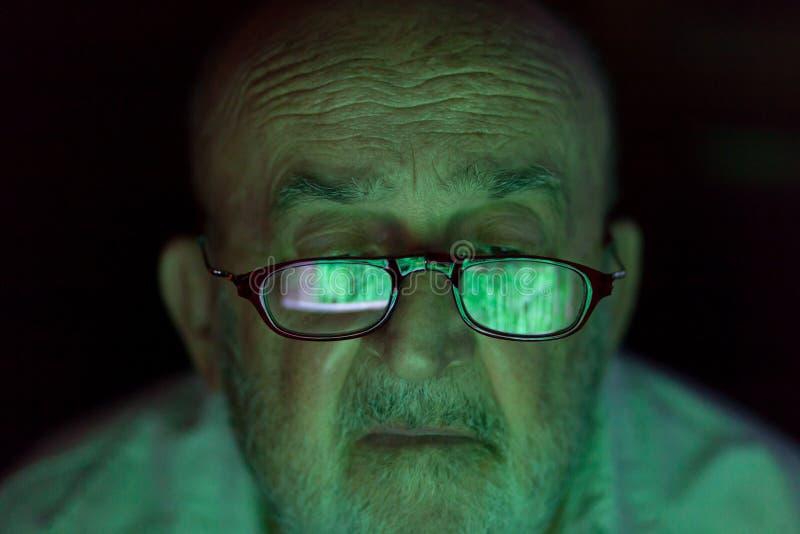Viejo hombre que mira una pantalla de ordenador cortada fotografía de archivo