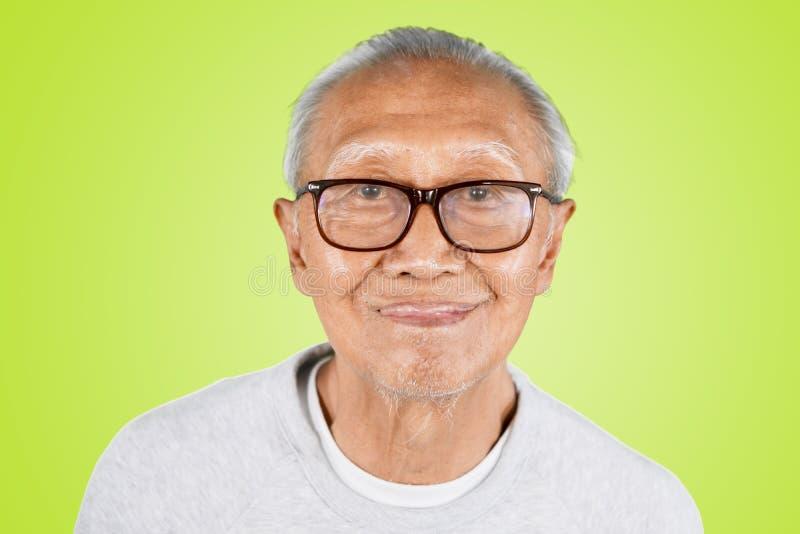 Viejo hombre que muestra su lengua en el estudio foto de archivo