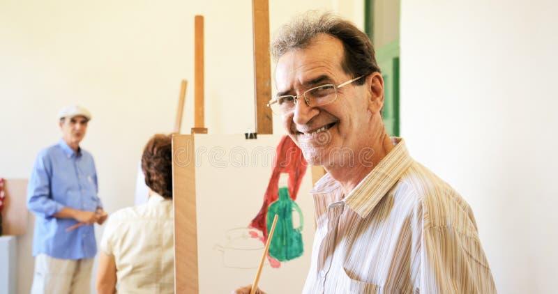 Viejo hombre que pinta a gente mayor feliz en Art School imagen de archivo