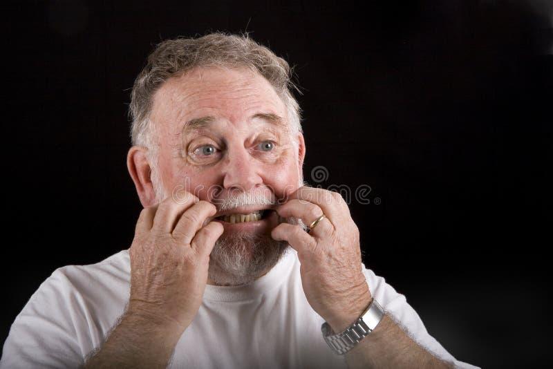 Viejo hombre que rasguña la cara foto de archivo