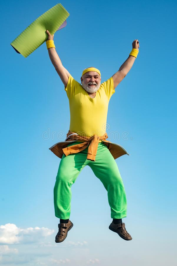 Viejo hombre que salta en fondo del cielo azul Concepto del retiro de la libertad Salto divertido del hombre mayor imagen de archivo libre de regalías