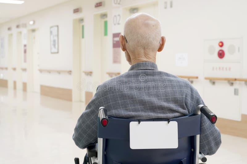 Viejo hombre que se sienta en la silla de ruedas en hospital fotografía de archivo
