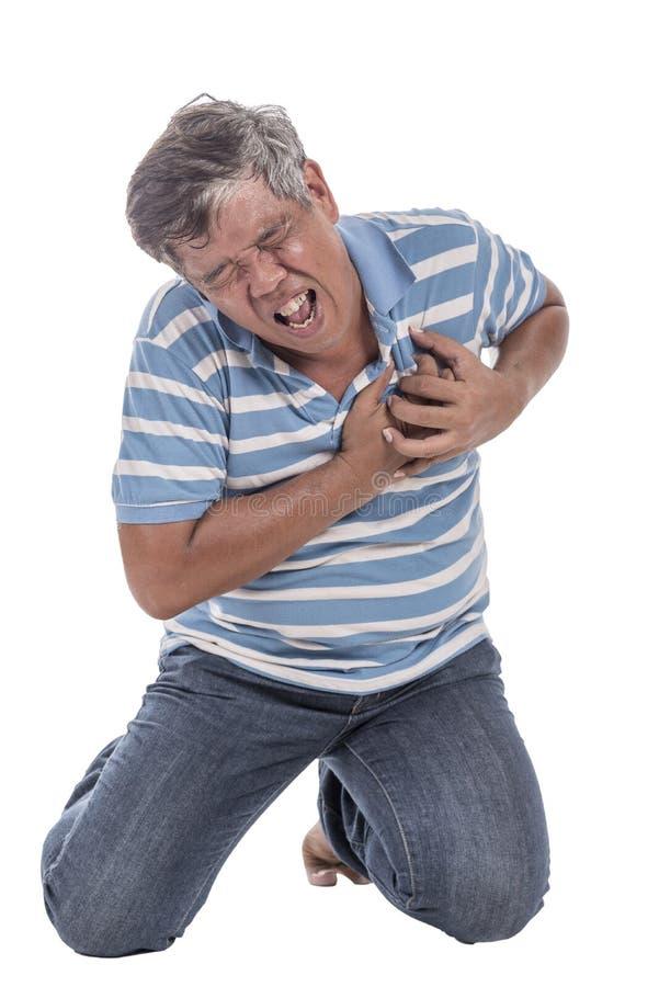 Viejo hombre que se sienta en las rodillas con dolor de pecho imagen de archivo