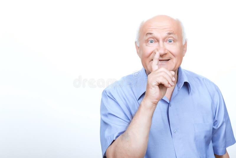 Viejo hombre que sostiene el finger delante de la boca imágenes de archivo libres de regalías