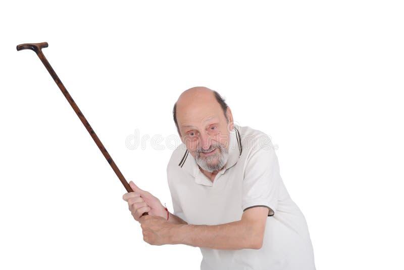 Viejo hombre que sostiene un bastón y que regaña alguien hacia la cámara fotos de archivo libres de regalías