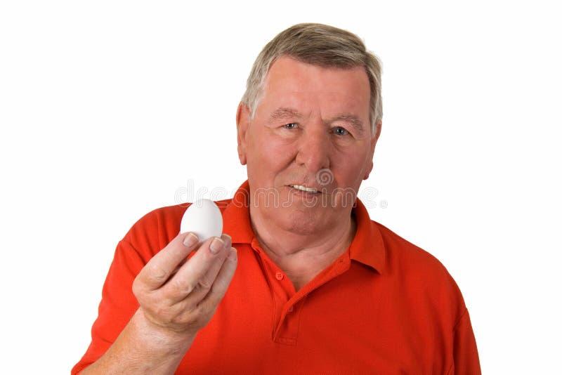 Viejo hombre que sostiene un huevo imagenes de archivo