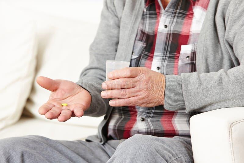 Viejo hombre que toma píldoras con agua imagen de archivo libre de regalías