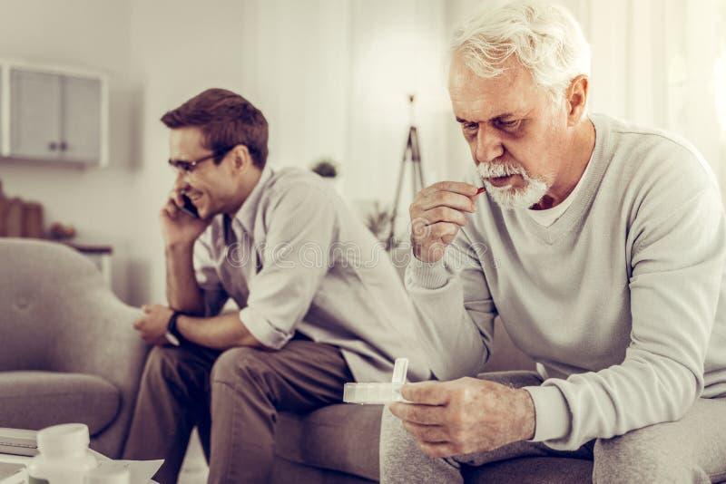Viejo hombre que toma píldoras mientras que hijo indiferente que tiene una llamada de teléfono fotos de archivo libres de regalías