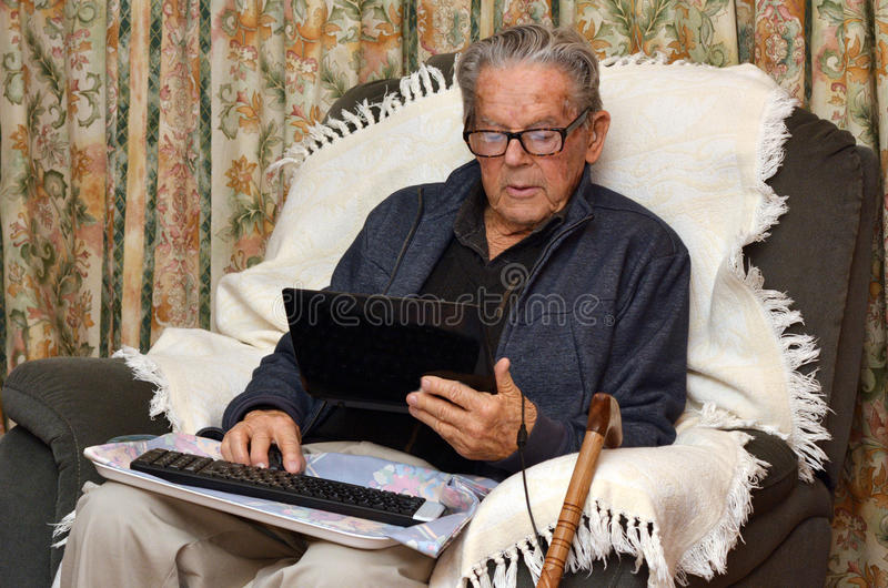 Viejo hombre que trabaja con el ordenador portátil en casa imágenes de archivo libres de regalías