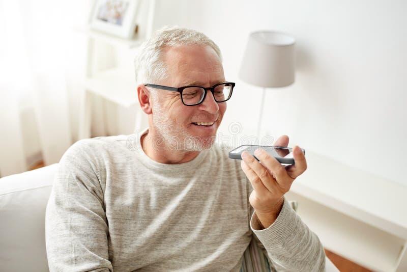 Viejo hombre que usa el registrador del control por voz en smartphone fotografía de archivo