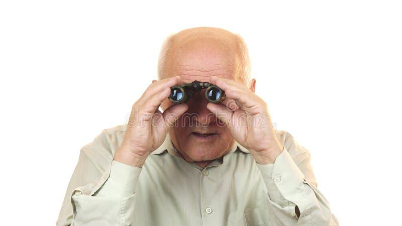 Viejo hombre que usa los prismáticos que parecen sorprendidos a la cámara foto de archivo