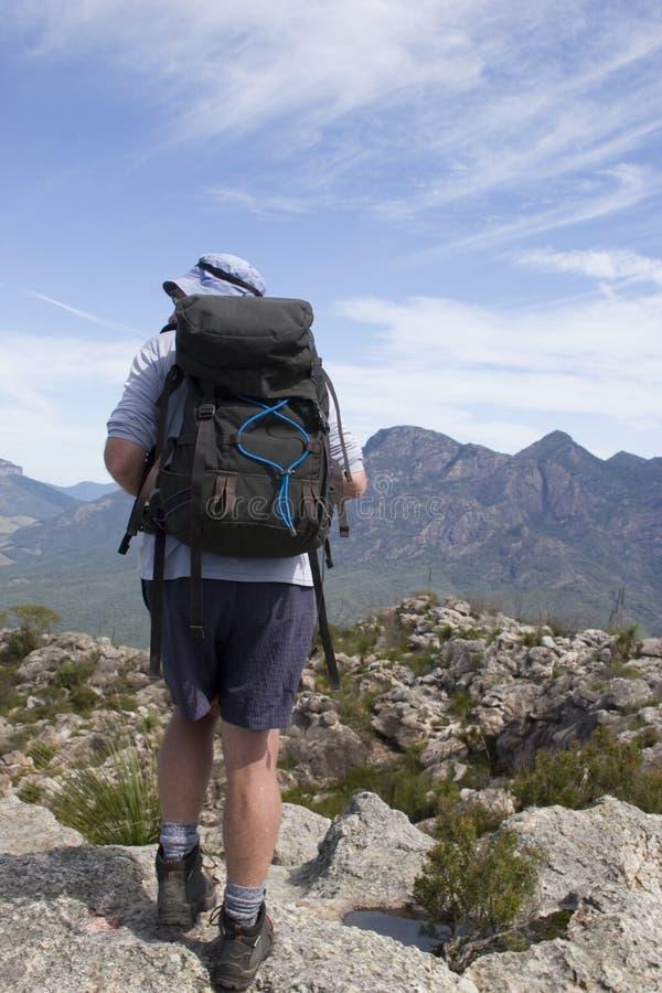 Viejo hombre que va de excursión en la tapa 2 de la montaña imagen de archivo