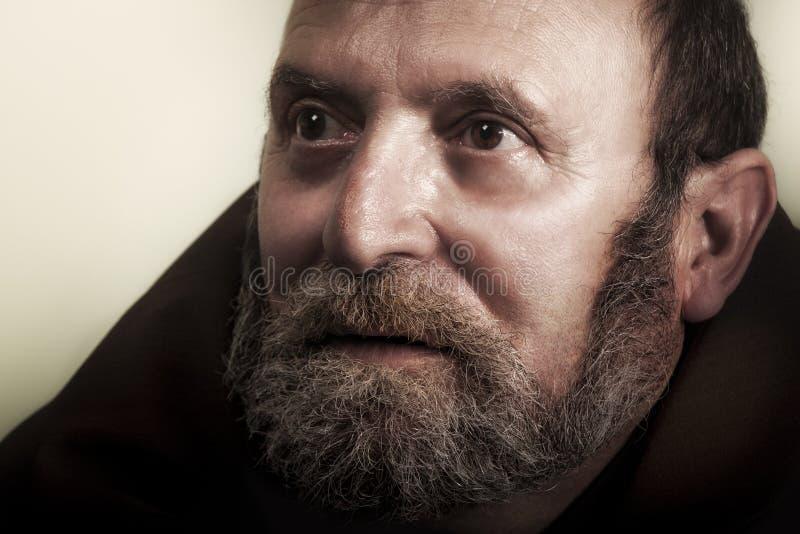 Viejo hombre sin hogar con la barba que mira adelante imágenes de archivo libres de regalías