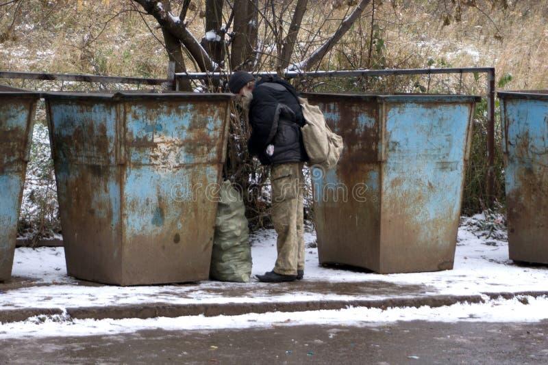 Viejo hombre sin hogar en la búsqueda para la comida Vagabundo de los pobres hambriento, revolviendo para un poco de comida en ba fotografía de archivo