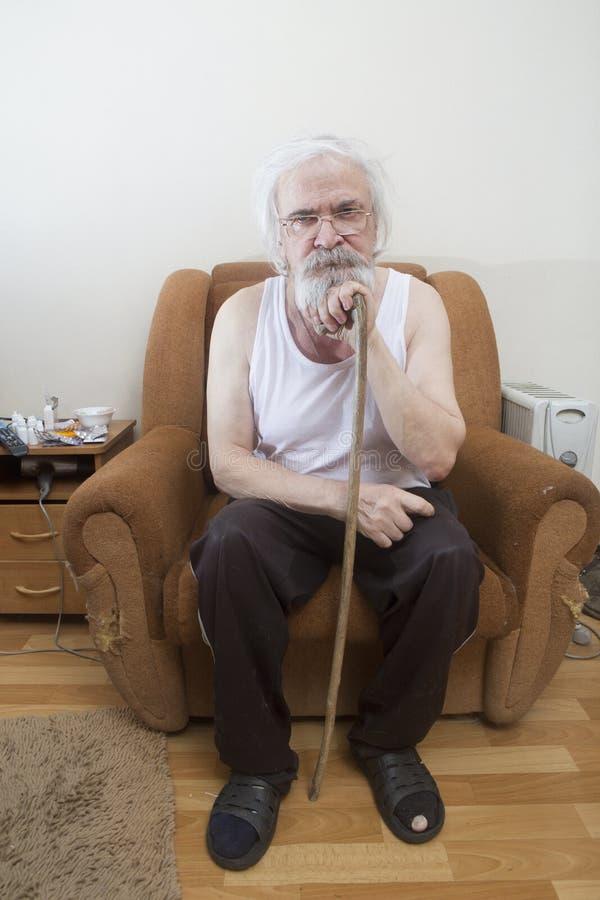 Viejo hombre solo enfermo en la butaca en casa fotos de archivo
