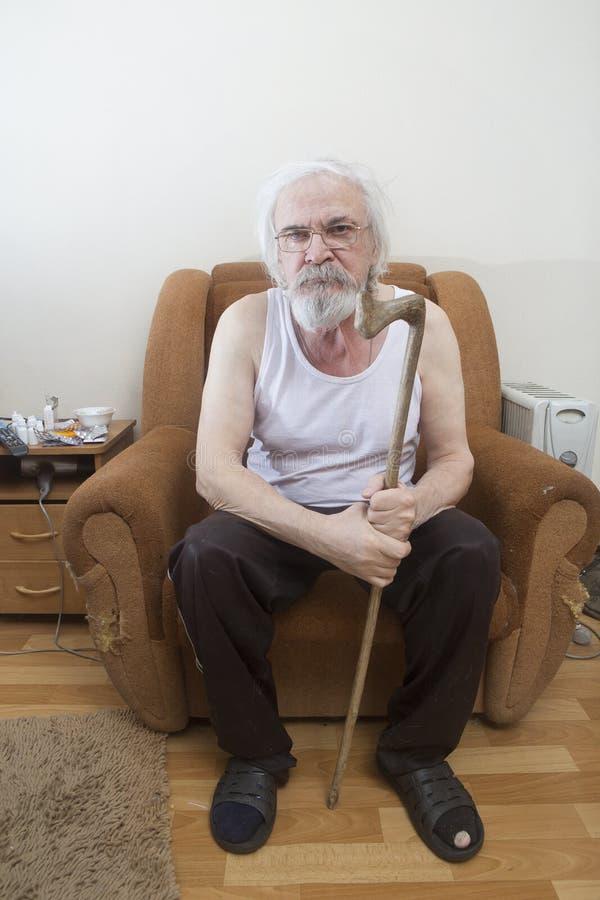 Viejo hombre solo enfermo en la butaca en casa imagen de archivo libre de regalías