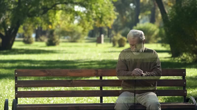 Viejo hombre solo que desaparece del banco, concepto de la muerte, transience de la vida fotos de archivo libres de regalías