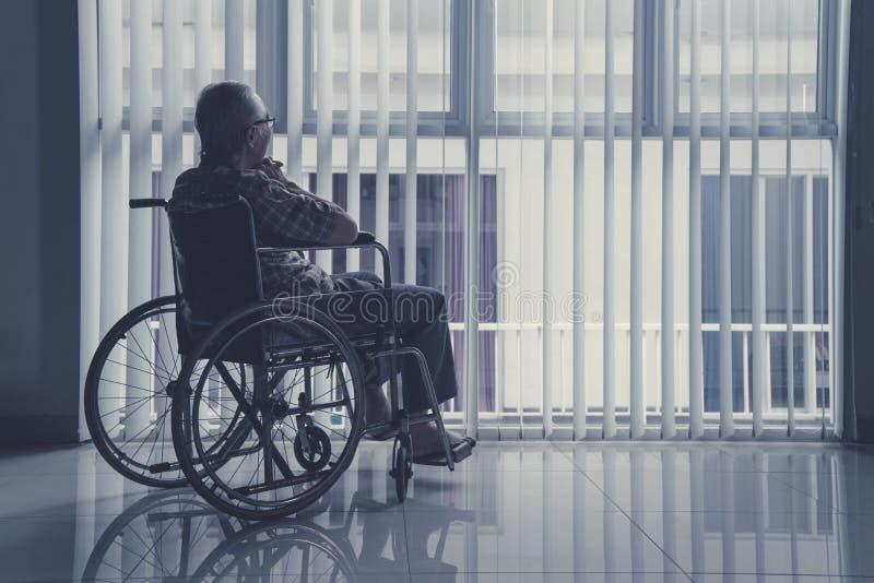 Viejo hombre solo que se sienta en la silla de ruedas en casa fotos de archivo libres de regalías