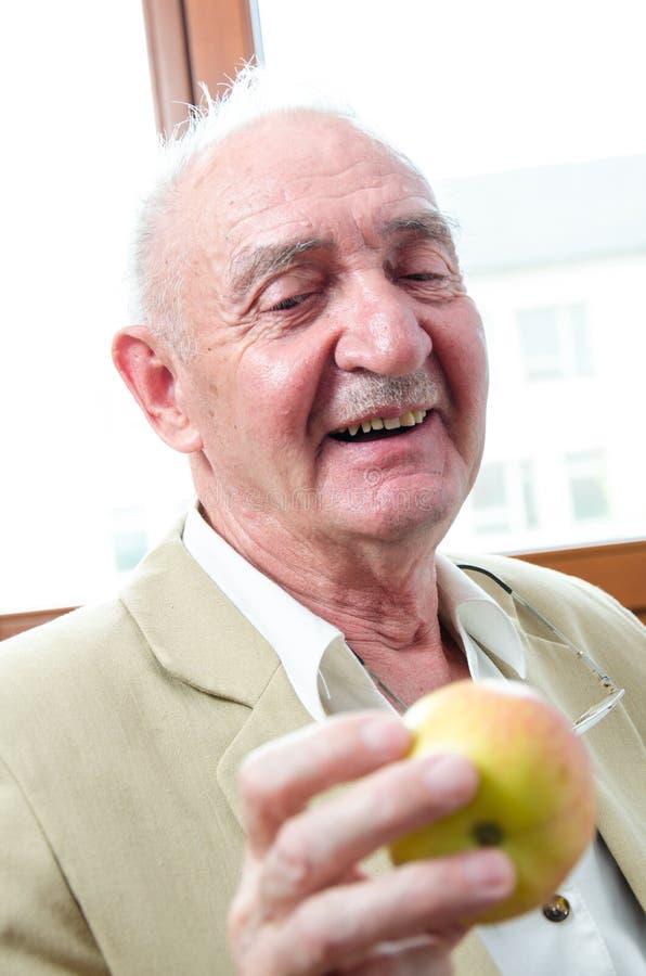 Viejo hombre sonriente con la manzana fotografía de archivo libre de regalías