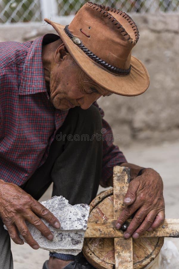 Viejo hombre tibetano que limpia la rueda de rezo de madera antigua foto de archivo