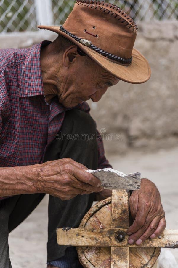 Viejo hombre tibetano que limpia la rueda de rezo de madera antigua imagen de archivo libre de regalías