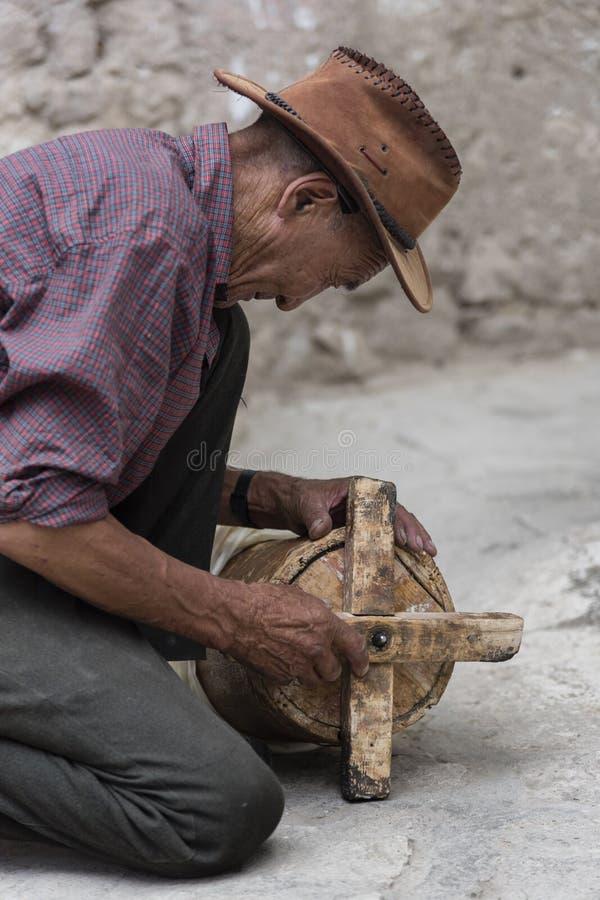 Viejo hombre tibetano que repara la rueda de rezo de madera antigua fotos de archivo
