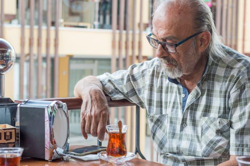 Viejo hombre turco con las lentes que miran su smartpone mientras que bebe té turco en un restaurante fotografía de archivo libre de regalías