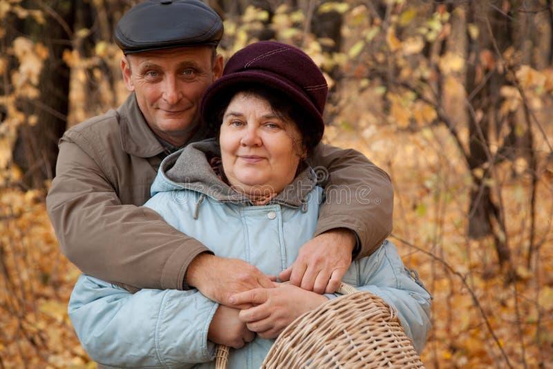 Viejo hombre y mujer mayor con la cesta en delantera otoñal imagenes de archivo