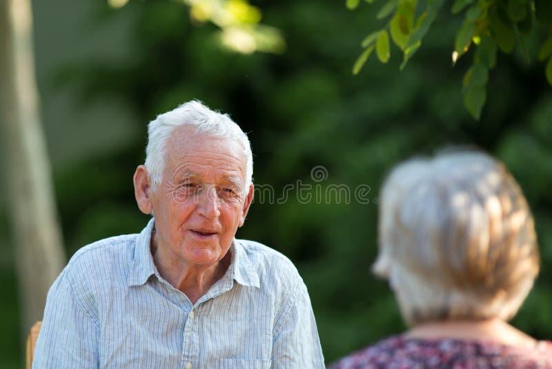 Viejo hombre y mujer que hablan en parque imagen de archivo