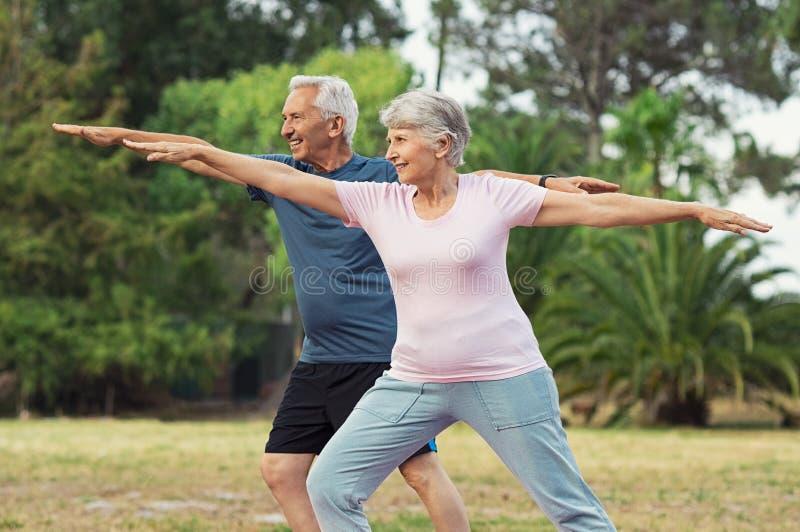 Viejo hombre y mujer que hacen estirando ejercicio fotos de archivo libres de regalías