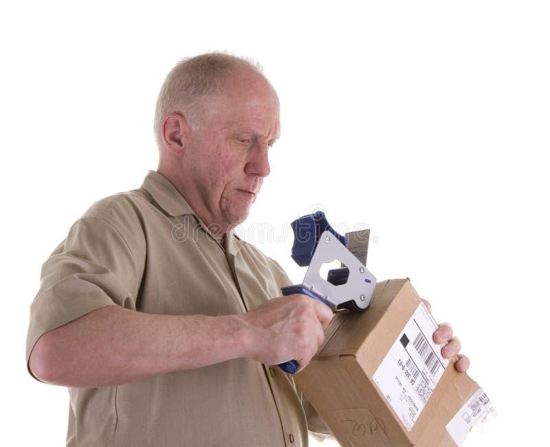 Viejo individuo en la camisa de Brown que sujeta con cinta adhesiva un rectángulo imagen de archivo libre de regalías