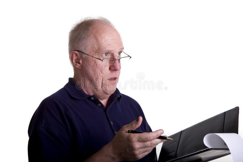 Viejo individuo que explica reparto en cuaderno imágenes de archivo libres de regalías