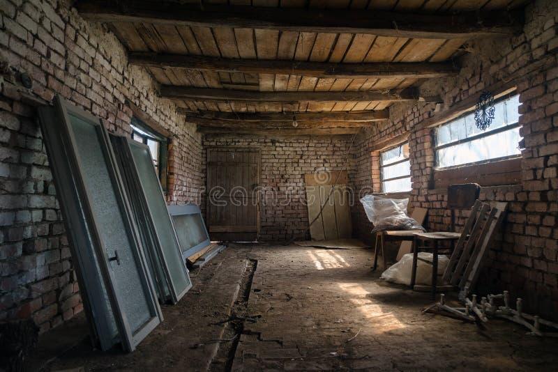 Viejo interior del granero en el pueblo Vertiente del vintage construida de la madera y del ladrillo, granero abandonado Dentro d foto de archivo libre de regalías